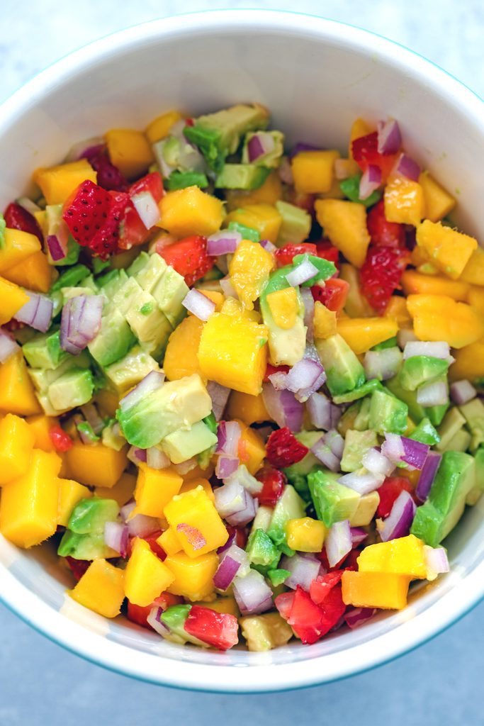 Overhead view of bowl of fruit salsa with chopped mango, strawberry, avocado, and red onion