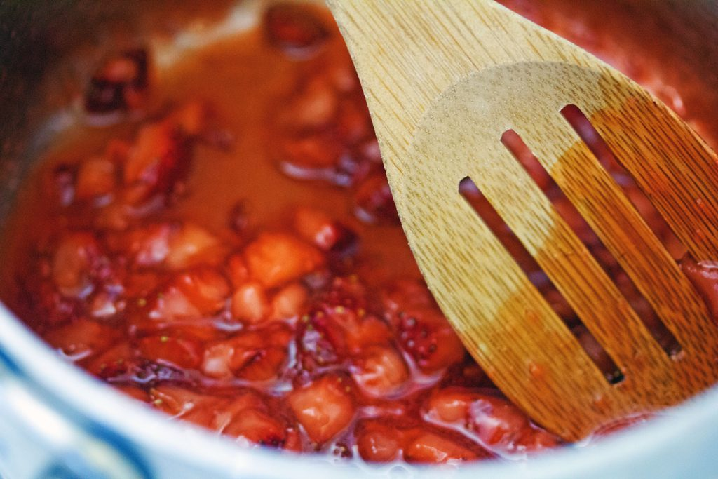 Overhead view of strawberry filling thickening in saucepan with wooden spoon