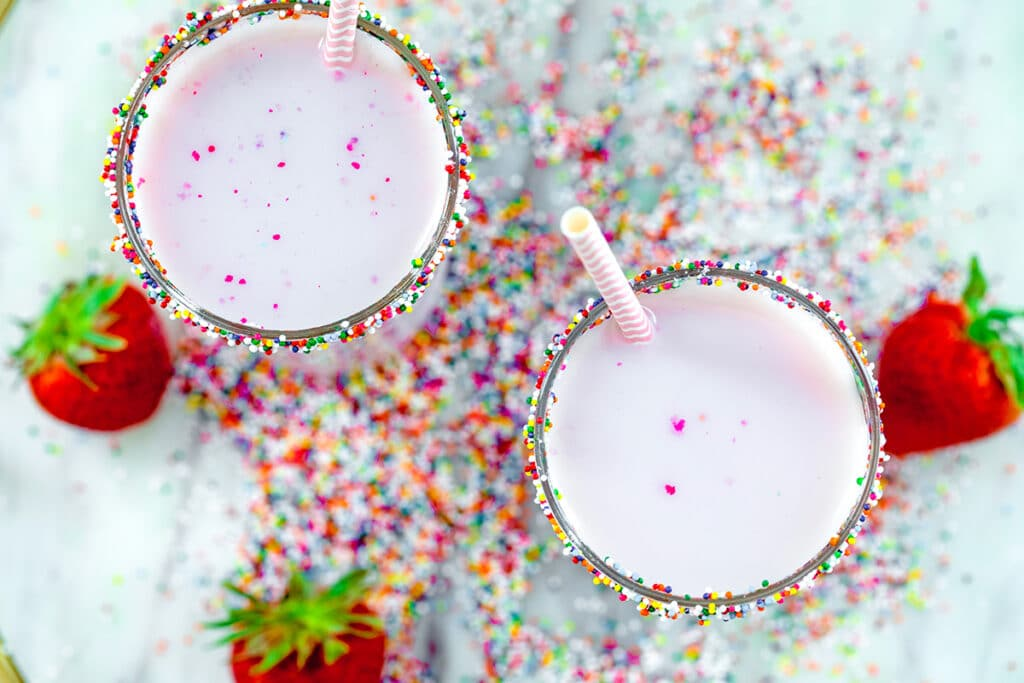 Overhead view of two glasses of pink strawberry milk on a marble tray with rainbow sprinkles and strawberries all around