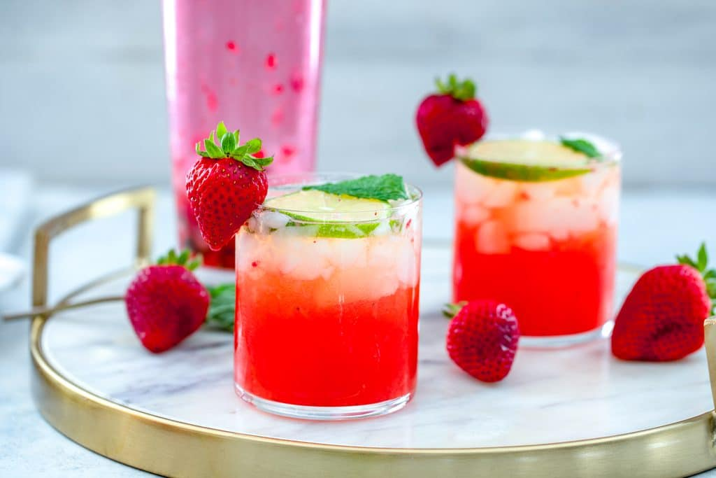 Landscape view of two strawberry mojitos on a marble tray with strawberries scattered around and a pink cocktail shaker in the background