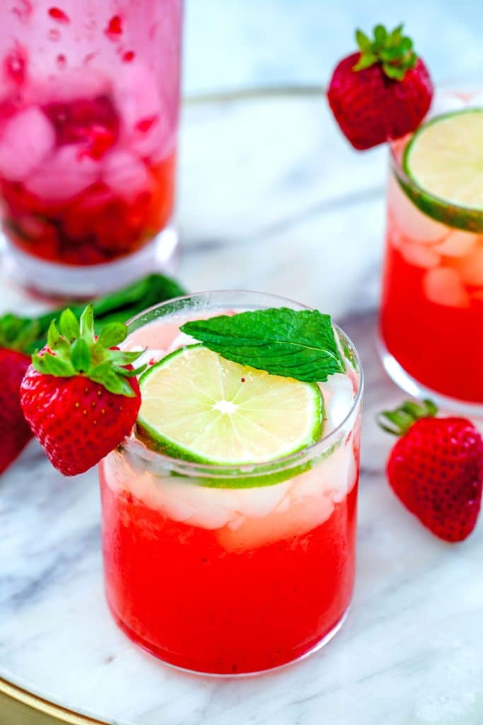 Head-on view of strawberry mojitos on a marble tray with lime, strawberry, and mint garnishes and a pink shaker in the background