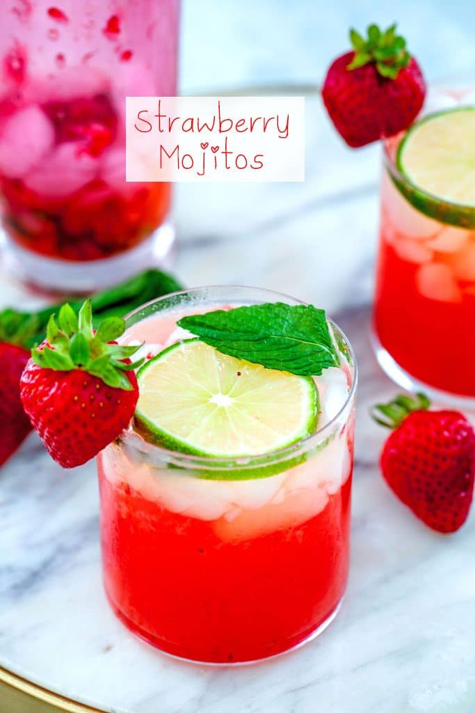 """Head-on view of strawberry mojitos on a marble tray with lime, strawberry, and mint garnishes and a pink shaker in the background with """"Strawberry Mojitos"""" text at top"""