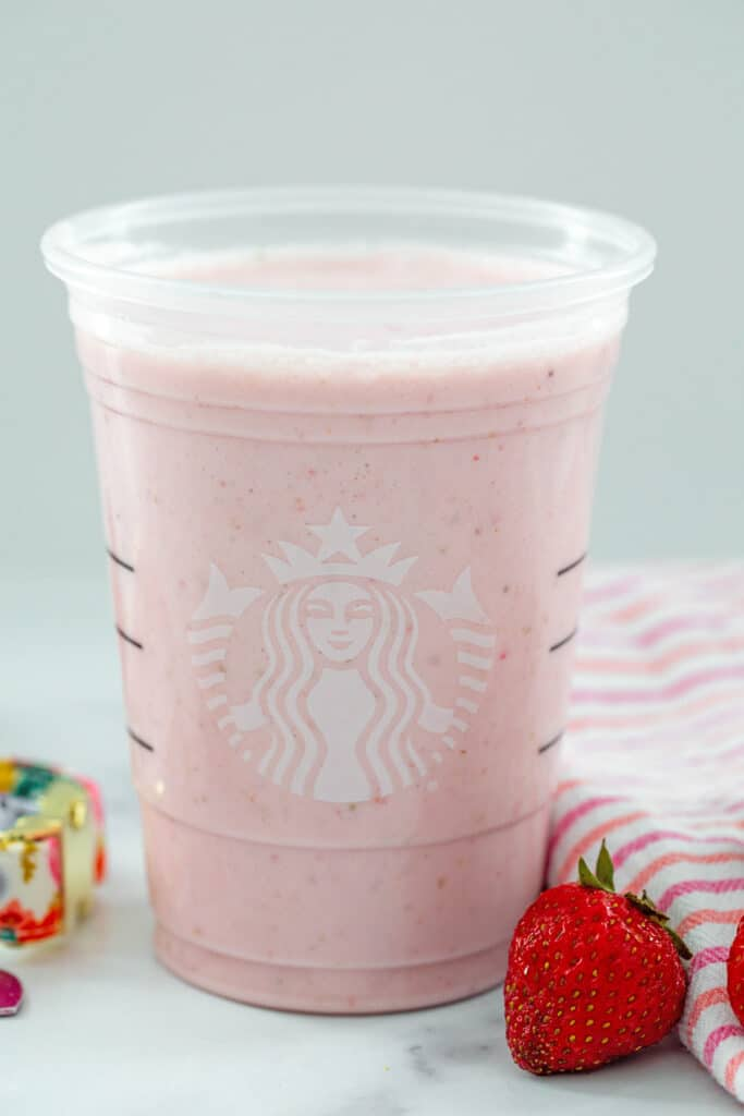 Head-on view of strawberry puppuccino mixture in a Starbucks cup with strawberries next to it