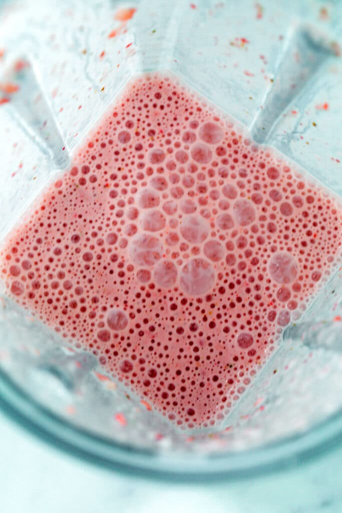 Overhead view of strawberry puppuccino mixture in a blender
