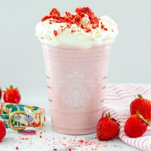 Head-on closeup view of a strawberry Puppuccino with fresh strawberries all around and crushed freeze-dried strawberries on top
