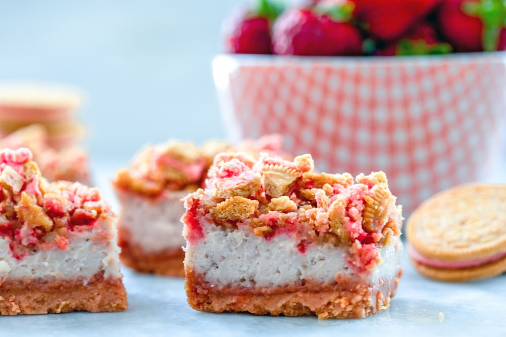 Landscape view of strawberry shortcake cheesecake bars with red bowl filled with strawberries and Oreo Cookie in the background