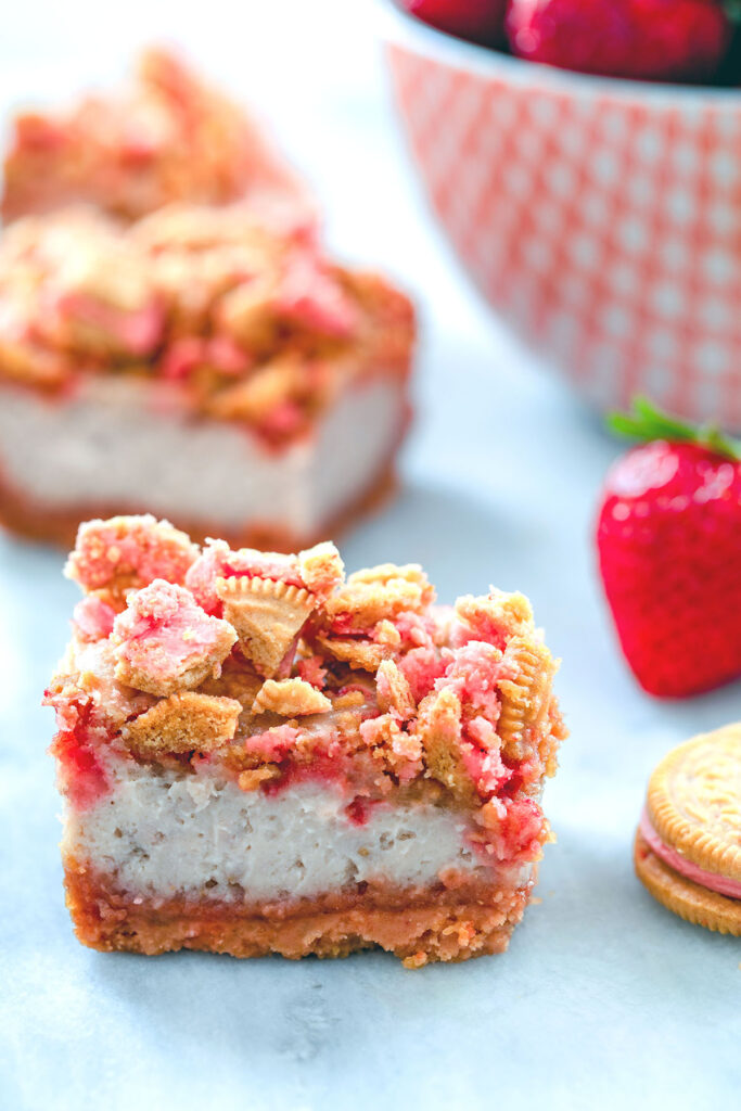 Head-on view of strawberry shortcake cheesecake bars with cookie crumbles and bowl of strawberries in the background