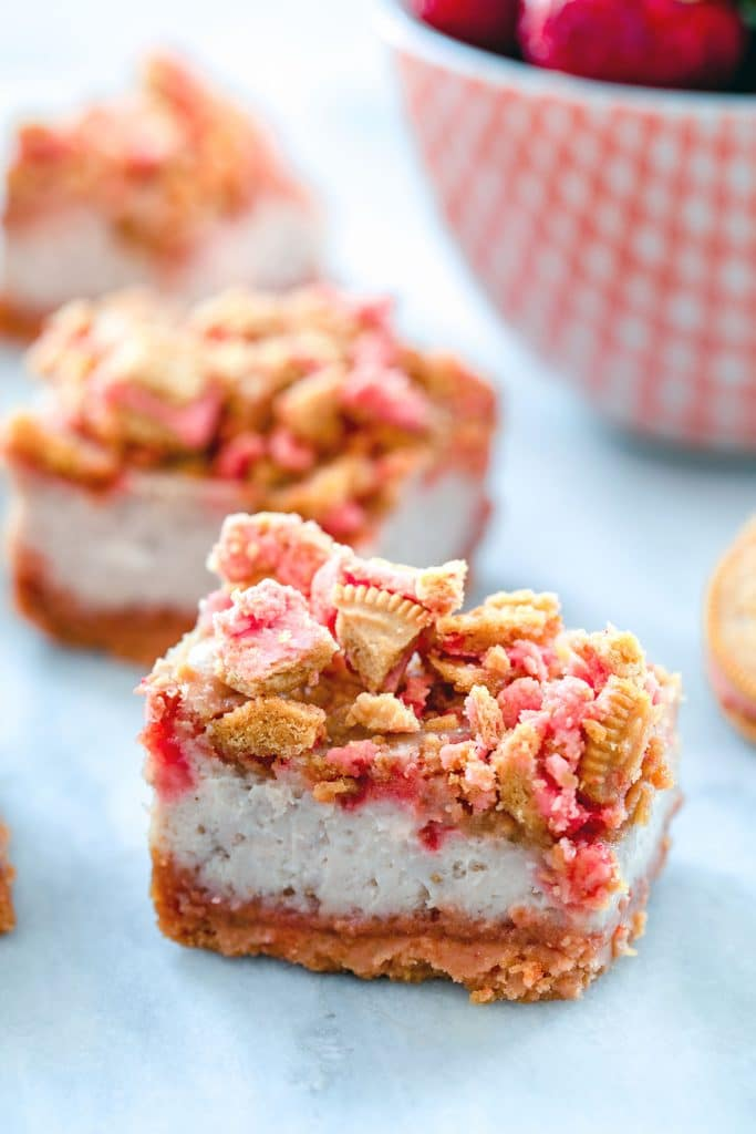 Up-close head-on view of strawberry shortcake cheesecake bar with more in the background and red bowl filled with strawberries
