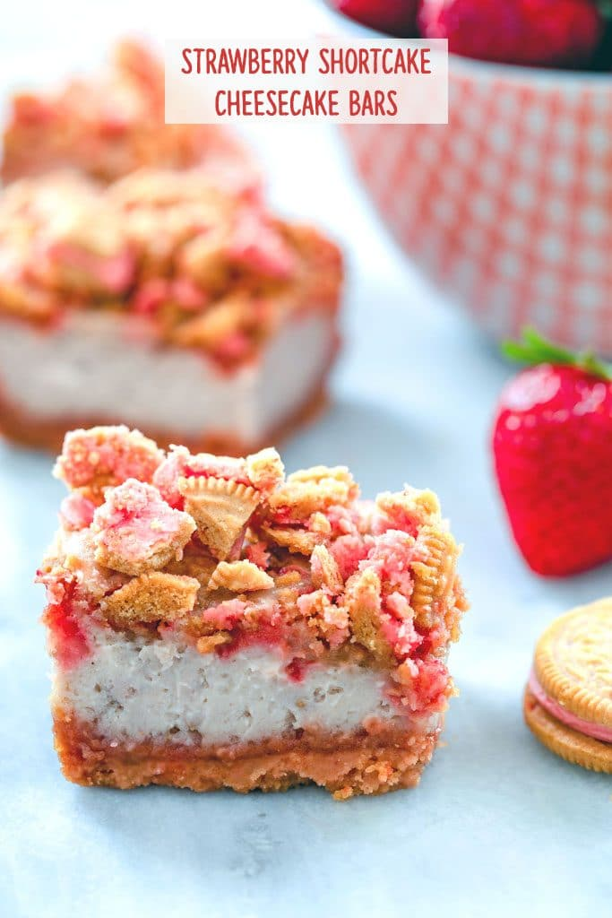 "Head-on view of strawberry shortcake cheesecake bars with cookie crumbles and bowl of strawberries in the background with ""Strawberry Shortcake Cheesecake Bars"" text at top"