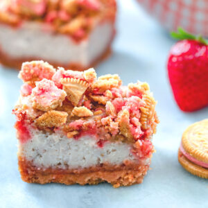 Head-on view of a strawberry shortcake cheesecake bar with strawberry shortcake oreo topping