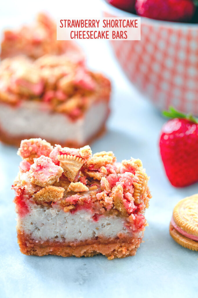 """Head-on view of strawberry shortcake cheesecake bars with cookie crumbles and bowl of strawberries in the background with """"Strawberry Shortcake Cheesecake Bars"""" text at top"""
