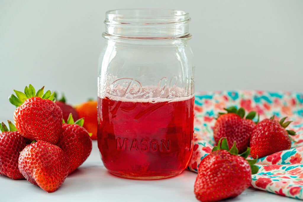 Head-on landscape view of a mason jar of strawberry simple syrup with whole strawberries all around