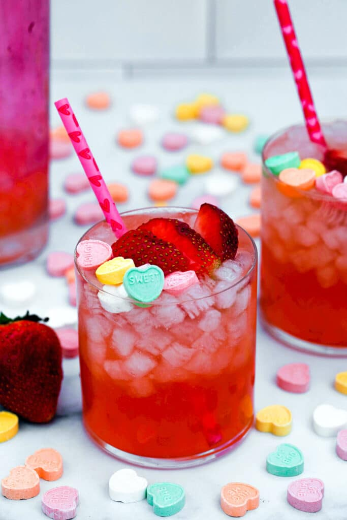 Closeup view of a strawberry vanilla cocktail topped with sliced strawberries and conversation hearts with second cocktail, strawberries, and conversation hearts in background