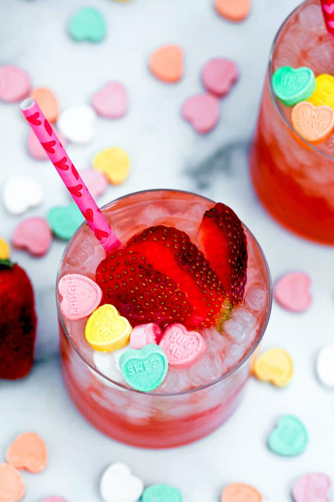 Overhead view of strawberry vanilla cocktail with focus on sliced strawberries and conversation hearts
