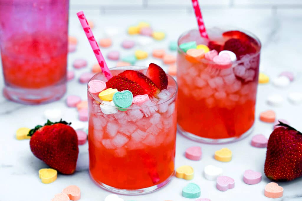 Landscape view of two strawberry vanilla cocktails with pink shaker in background and conversation hearts and strawberries all around