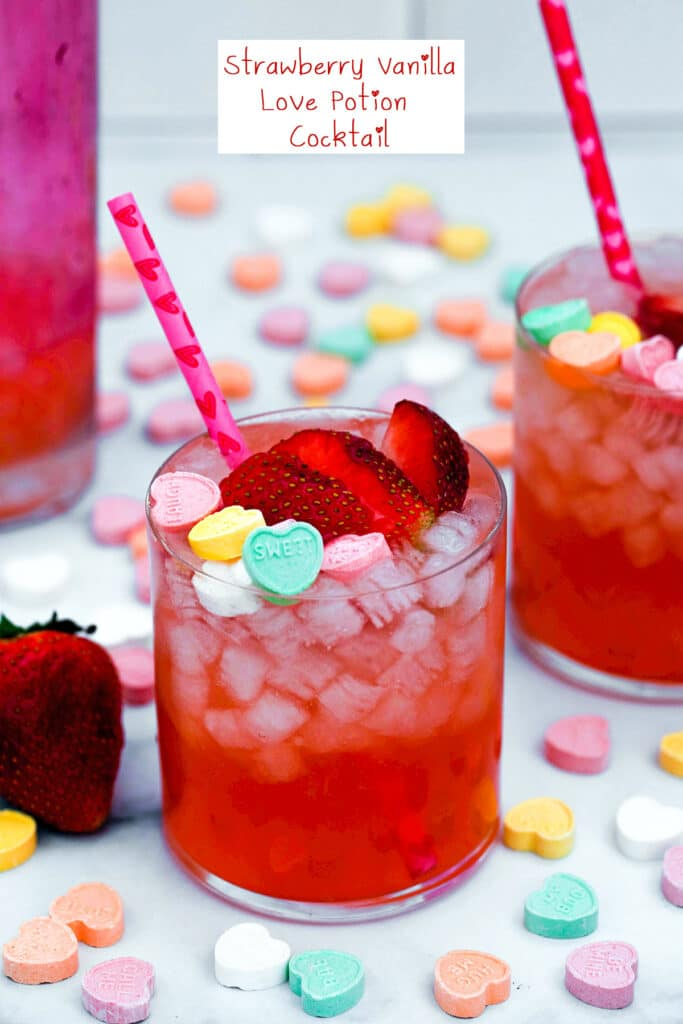 Closeup view of a strawberry vanilla cocktail topped with sliced strawberries and conversation hearts with second cocktail, strawberries, and conversation hearts in background and recipe title at top