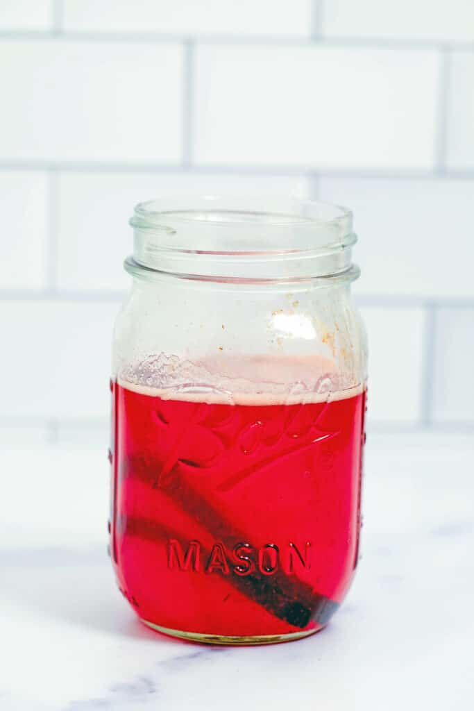 Head-on view of jar of strawberry vanilla simple syrup
