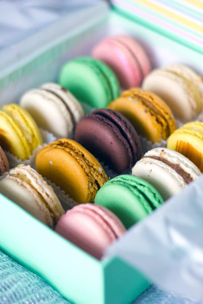 Overhead view of a box of colorful Sucré macarons