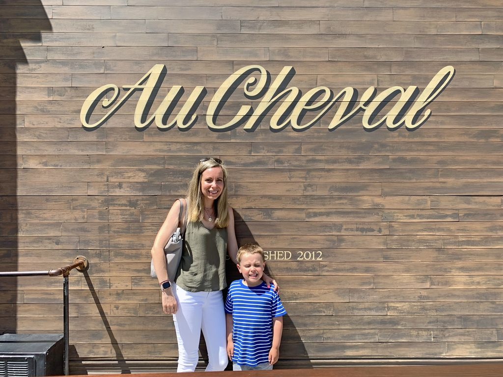 View of Sues and Henry standing outside of Au Cheval in Chicago
