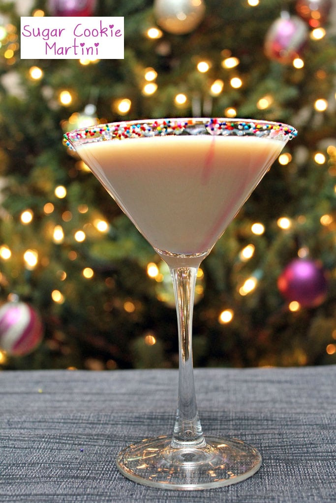 Head-on view of a sugar cookie martini with sprinkles rim in front of a lit Christmas tree with recipe title at top