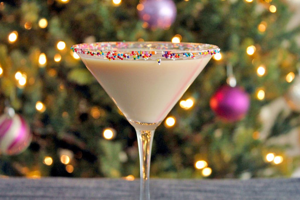 Landscape head-on view of sugar cookie martini with sprinkles rim in front of a lit Christmas tree