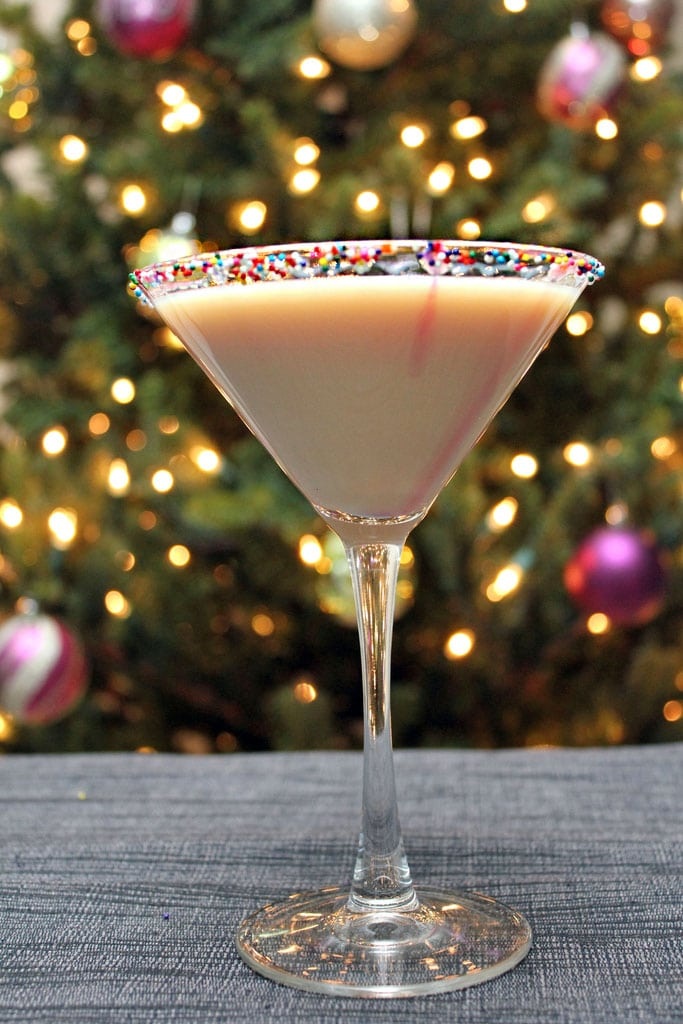 Head-on view of a sugar cookie martini with sprinkles rim in front of a lit Christmas tree