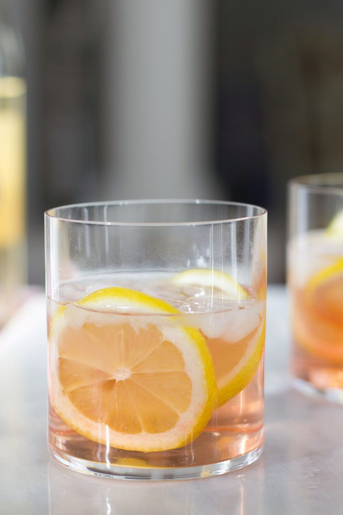A head-on view of a pink rosé spritzer in a rocks glass with lemon rounds on a white marble surface