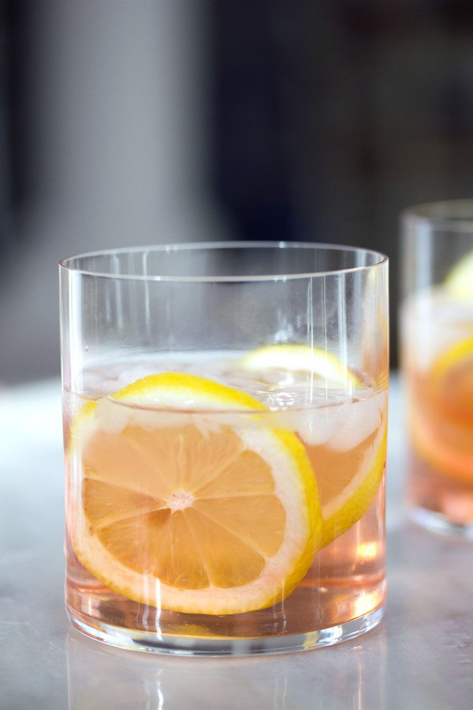 A head-on view of a pink rosé spritzer in a rocks glass with lemon rounds