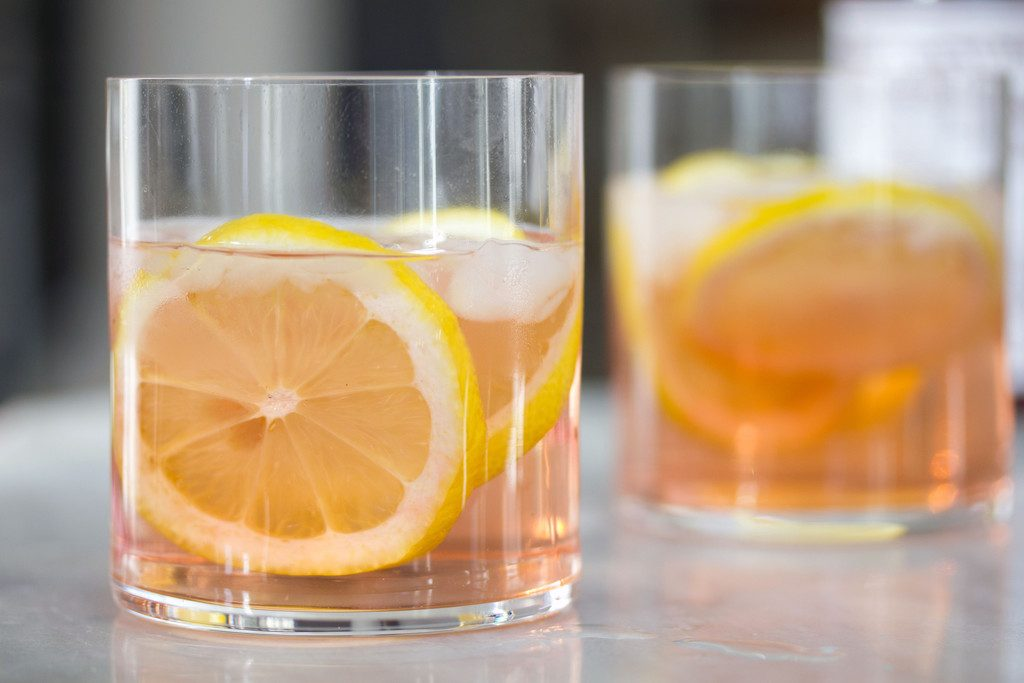 A landscape photo featuring two rocks glasses of pink rosé spritzer with lemon rounds on a white marble surface