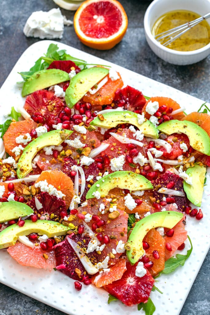 Overhead close-up view of winter citrus salad with blood oranges, cara cara oranges, grapefruit, fennel, avocado, goat cheese, and more with ingredients in the background