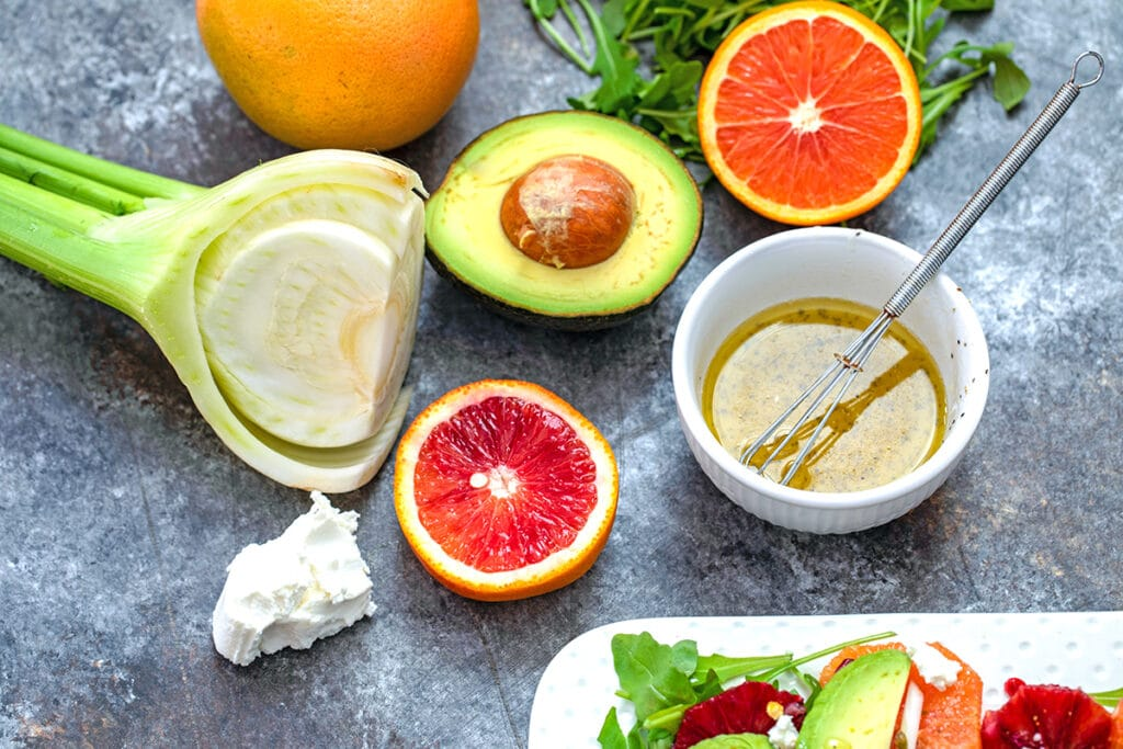 Overhead view of ingredients in salad, including fennel bulb, half an avocado, half a blood orange and grapefruit, hunk of goat cheese, arugula, and dressing in a white bowl with small whisk