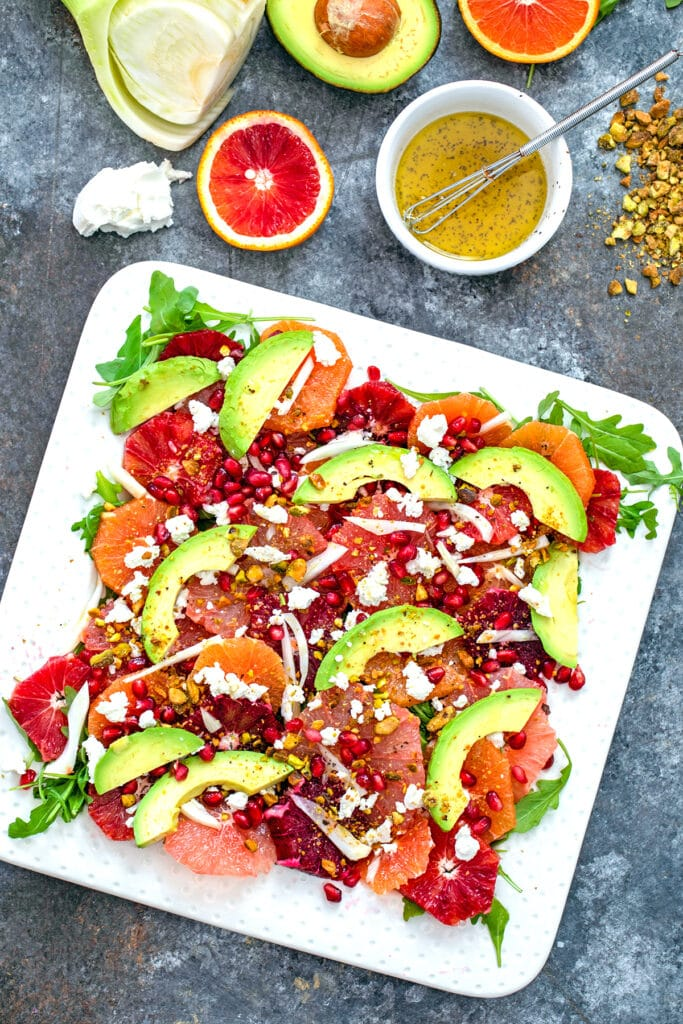 Bird's eye view of winter citrus salad with blood oranges, cara cara oranges, grapefruit, fennel, avocado, goat cheese, and more with some ingredients in the background