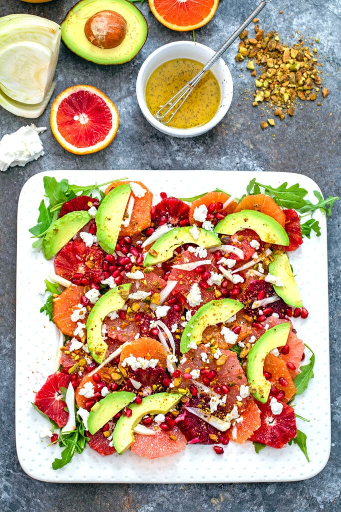Overhead view of winter citrus salad on a white platter with pistachios, blood orange half, grapefruit half, goat cheese, fennel bulb, half an avocado, and small white bowl of dressing