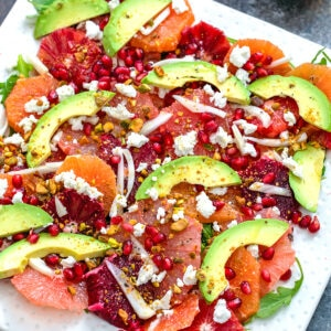 Close-up view of winter citrus salad featuring blood oranges, cara cara oranges, grapefruit, avocado, fennel, arugula, and goat cheese on white platter