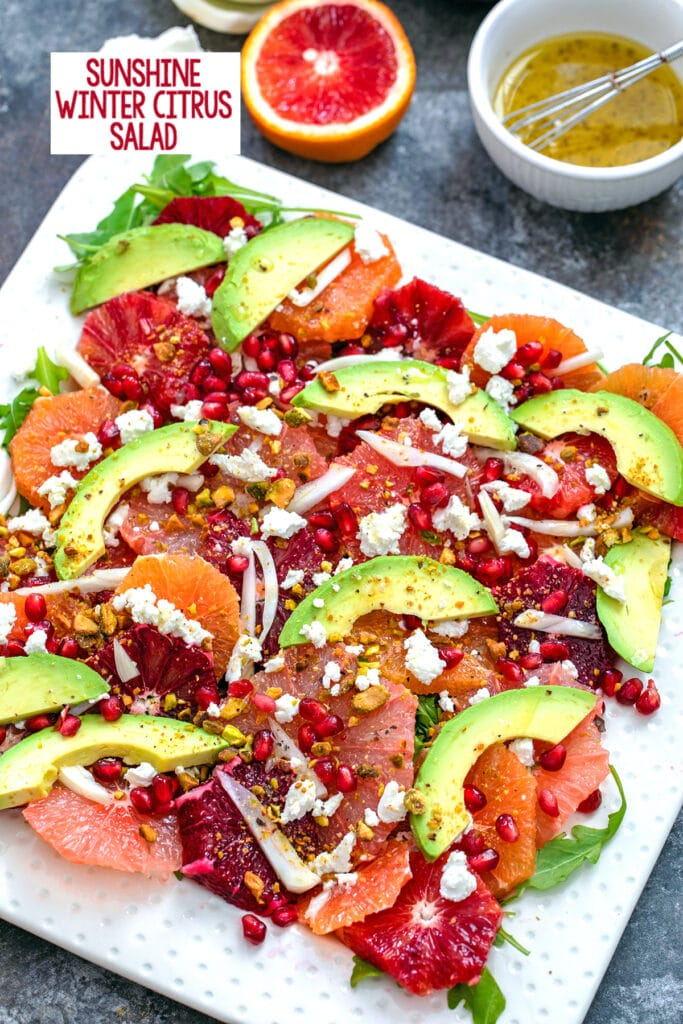 Overhead close-up view of winter citrus salad with blood oranges, cara cara oranges, grapefruit, fennel, avocado, goat cheese, and more with ingredients in the background and recipe title at top