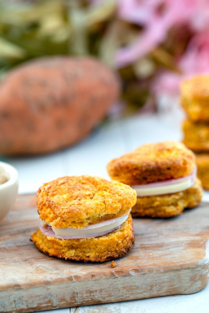 Sweet potato biscuit sandwiches on wooden board with whole sweet potato in background