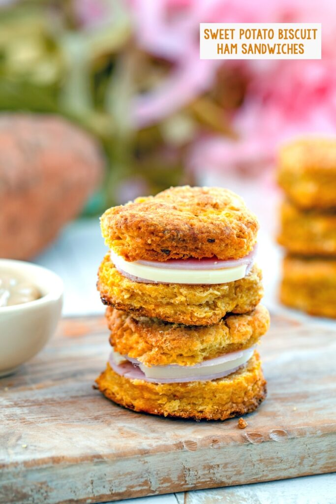 Head-on view of two sweet potato biscuit sandwiches on a wooden board with mustard and sweet potato in background and recipe title at top