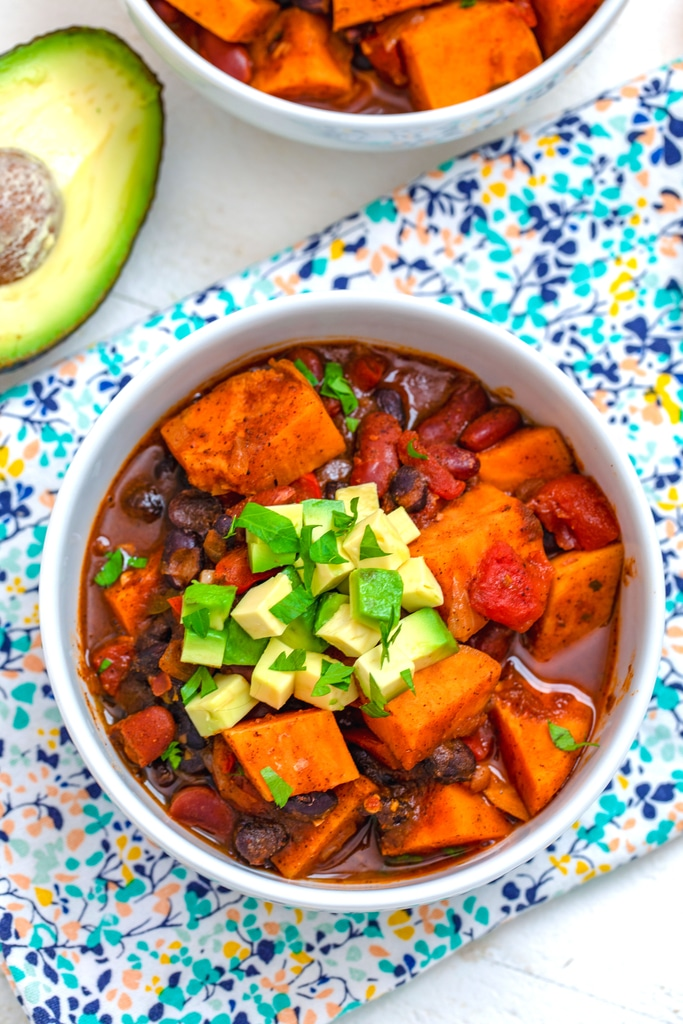 Overhead view of a bowl of sweet potato chili topped with avocado and cilantro with avocado in background