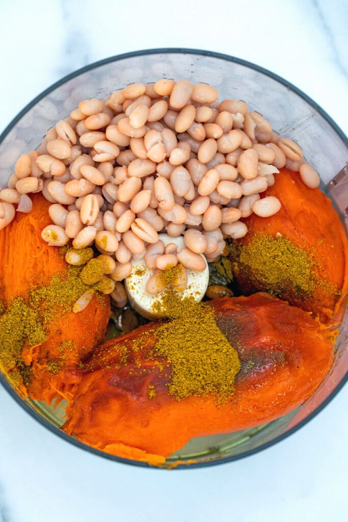 Overhead view of food processor with sweet potatoes, curry powder, spices, and beans