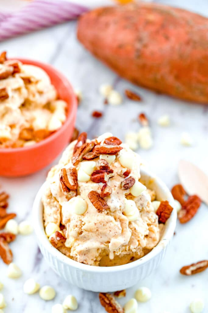 Overhead view of sweet potato ice cream topped with toasted pecans and white chocolate chips with whole sweet potato in the background