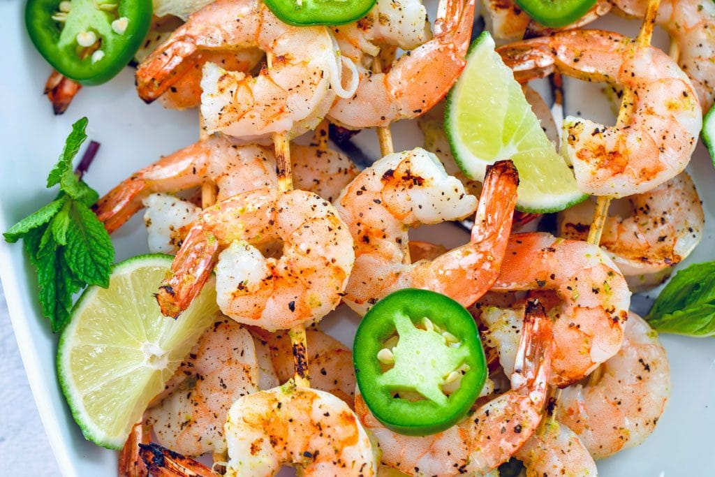 Landscape photo showing close-up of cooked tequila shrimp skewers with jalapeño slices, lime wedges, and mint leaves