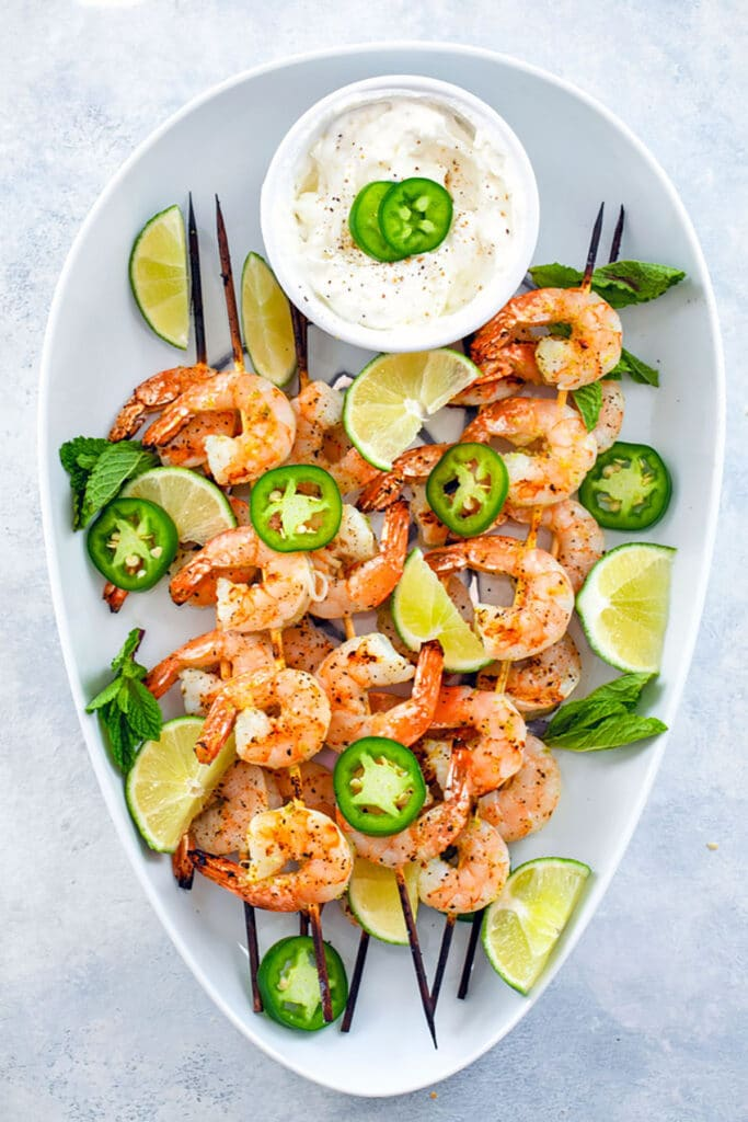 Bird's eye view from distance showing white platter with grilled tequila shrimp skewers with jalapeño slices, lime wedges, and yogurt dip in small bowl