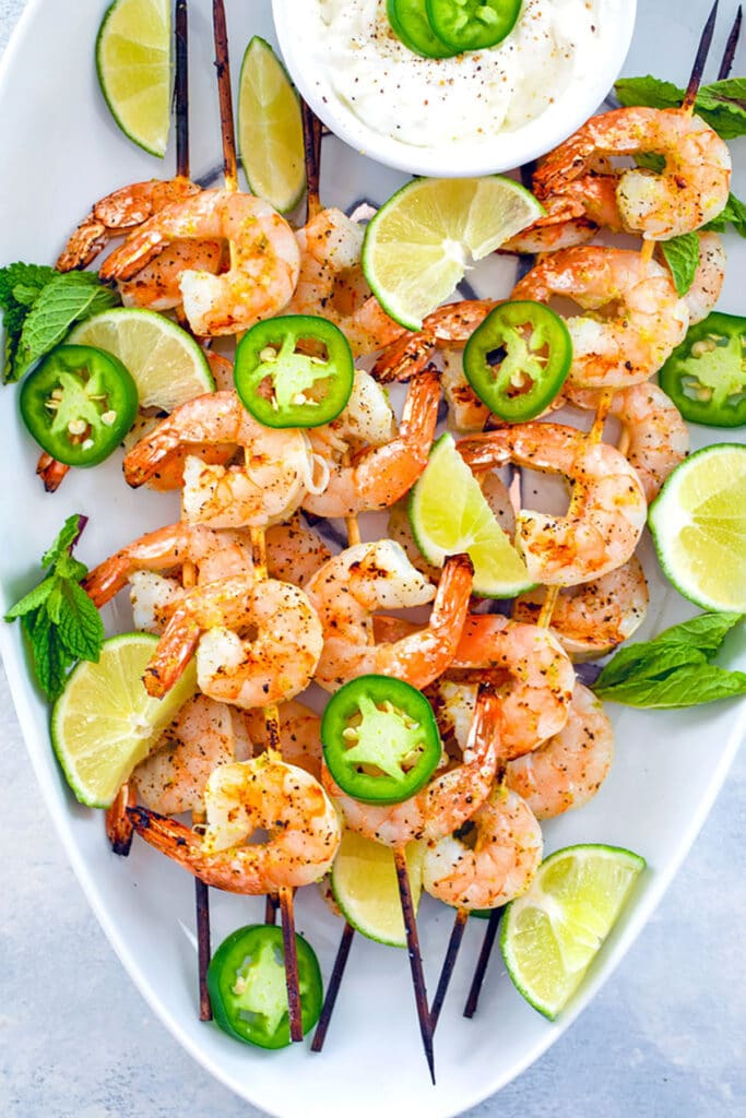 Bird's eye view of white platter with skewers of tequila shrimp with sliced jalapeños, lime wedges, and yogurt dip
