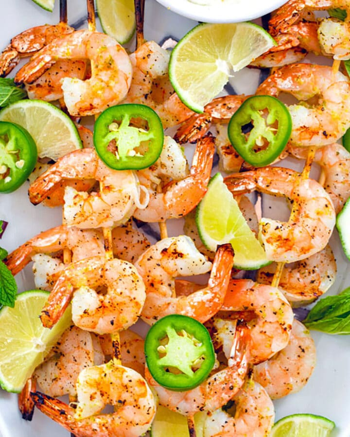 Bird's eye closeup view of white platter with skewers of tequila shrimp with sliced jalapeños, lime wedges, and yogurt dip
