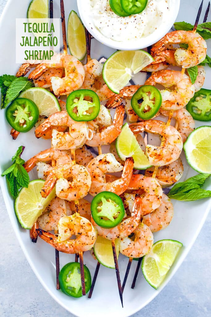 """Bird's eye view of white platter with skewers of tequila shrimp with sliced jalapeños, lime wedges, and yogurt dip with """"tequila jalapeño shrimp"""" text at top"""