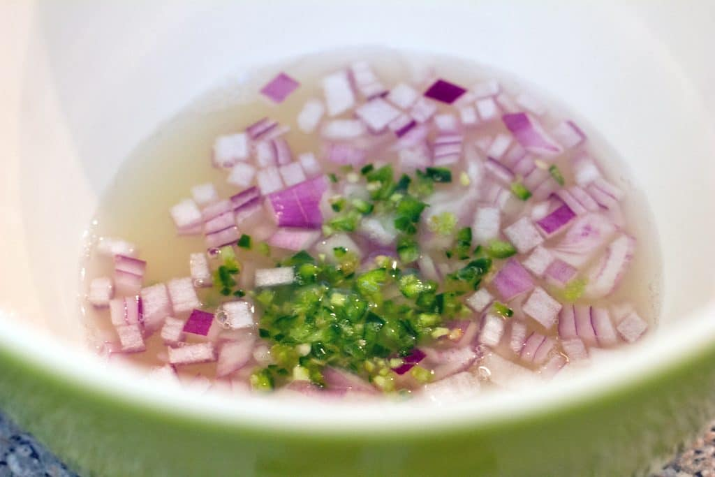 Overhead view of bowl with freshly squeezed lime juice with chopped jalapeño pepper and red onion