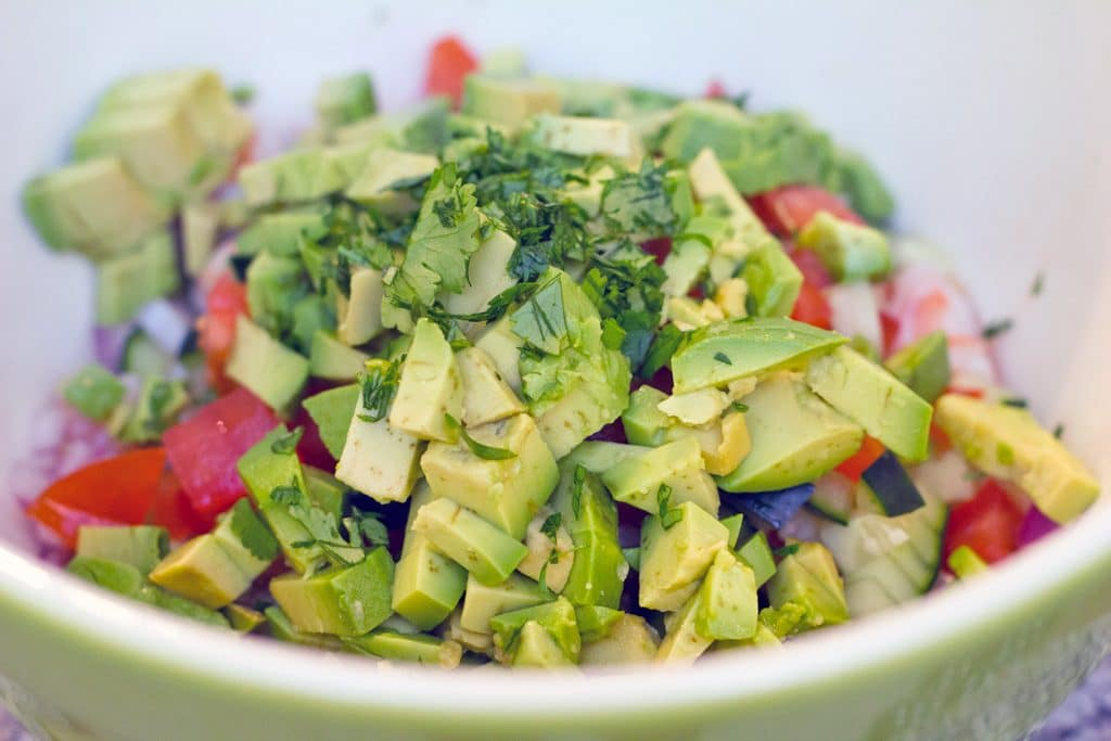 Head-on view of tomatoes, avocado, red onion, and cilantro in a bowl