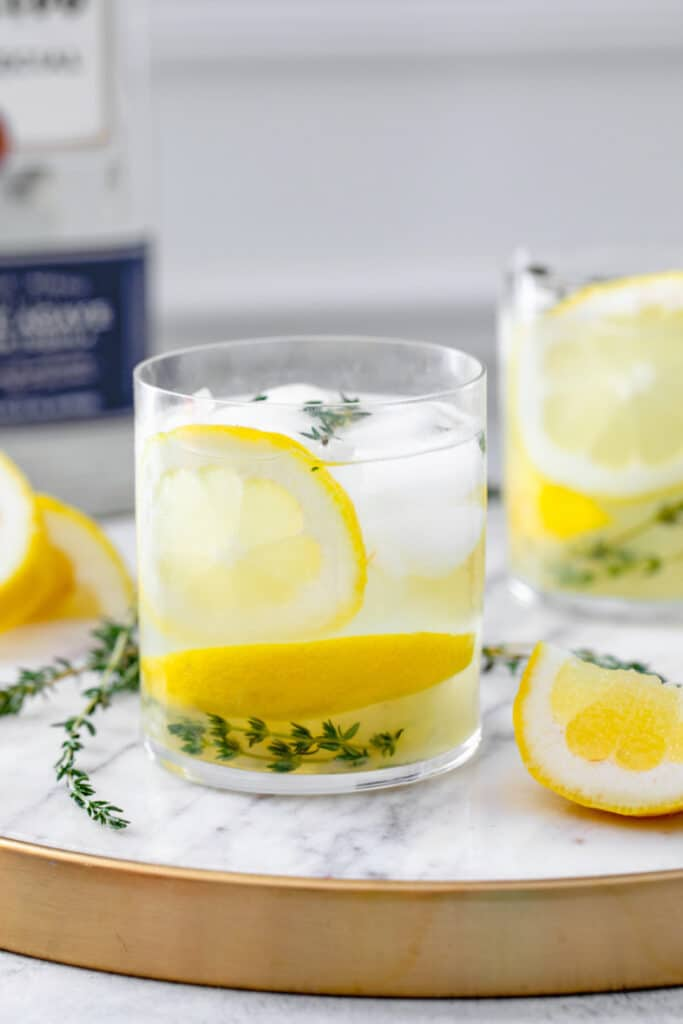 Head-on close-up view of a glass of tequila thyme lemonade with lemon rounds and fresh thyme with more lemons and thyme in background and recipe title at top