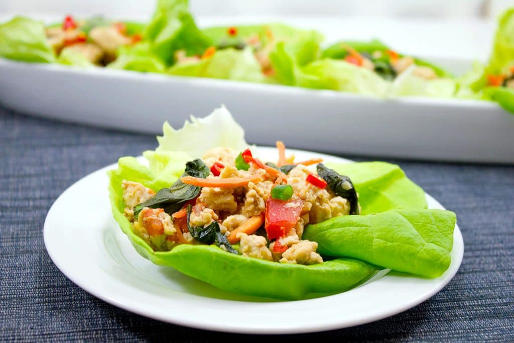 landscape photo of a white plate with a Thai chicken basil lettuce wrap on it and a platter with more lettuce wraps in the background