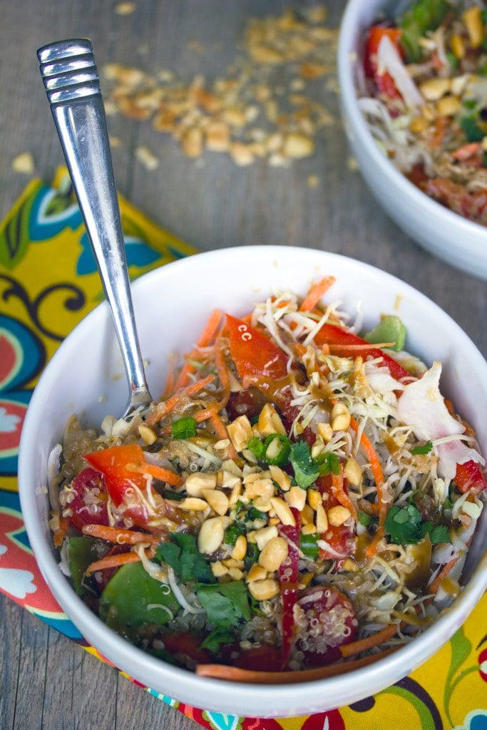 Overhead view of a white bowl of Thai quinoa salad with a fork on a colorful napkin with second bowl in the background and chopped peanuts all around
